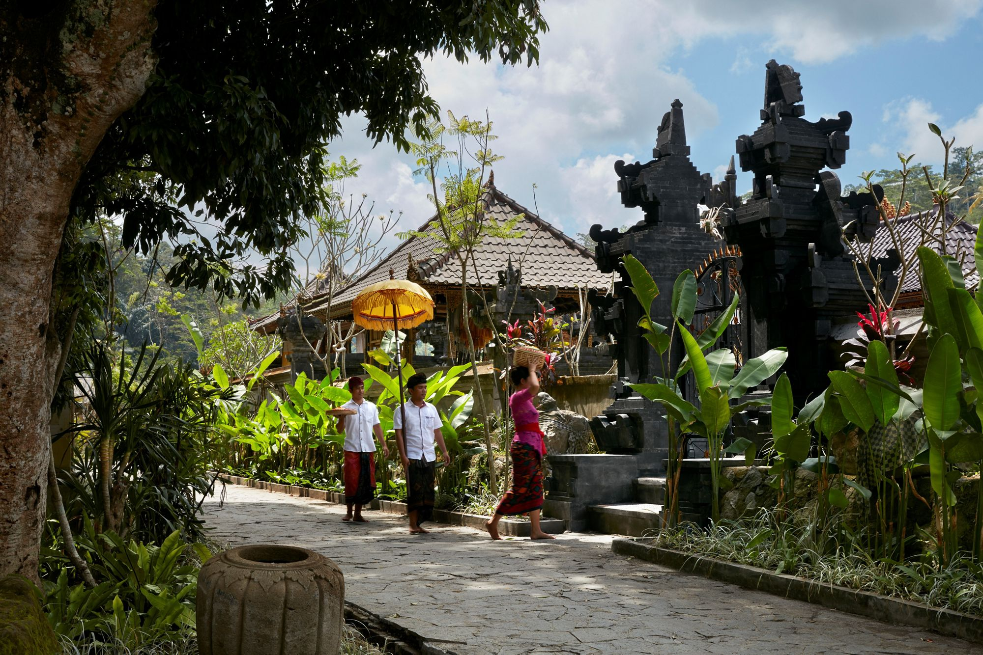 Mandapa Temple: A woman and two men on a paved walkway carrying offerings to a temple. Image courtesy of the Mandapa Resort.